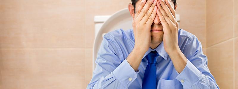 Probleme beim Wasserlassen: Mann sitzt mit Schmerzen beim Urinieren auf der Toilette.