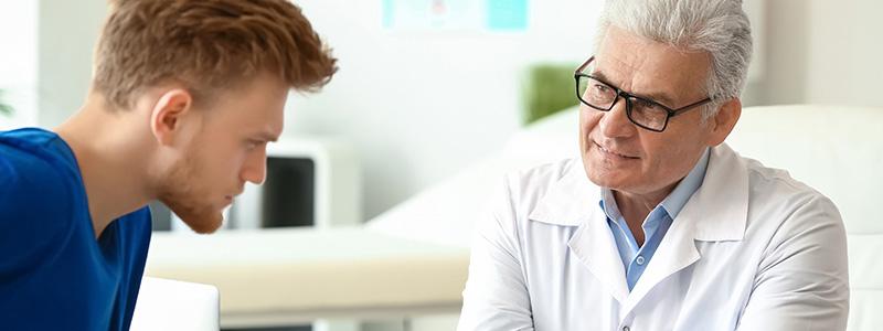 Ein Männerarzt erklärt seinem Patienten alles über die Andrologie.