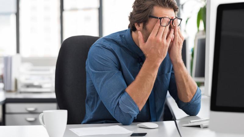 Psychische Risikofaktoren für Prostatitis: gestresster Mann am Arbeitsplatz.