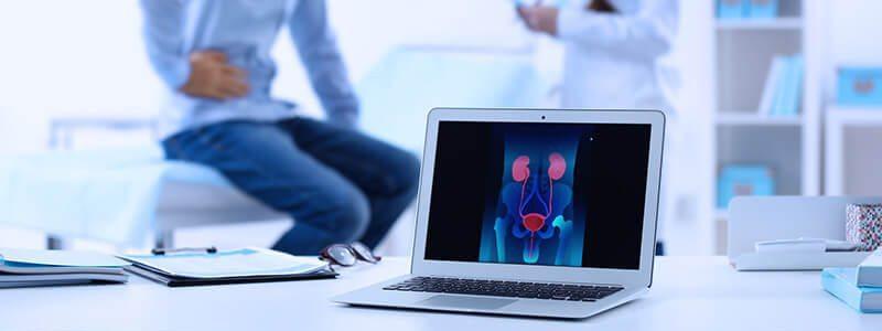 Schmerzen im Unterleib: Mann sitzt mit Prostataschmerzen beim Arzt.