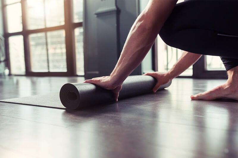 Mann will Beckenbodentraining machen und rollt dafür seine Gymnastikmatte aus.